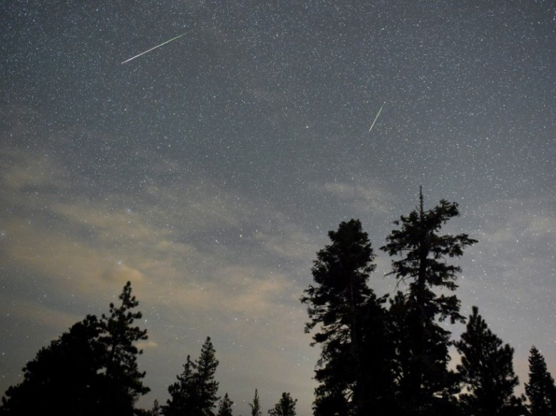 SPRING MOUNTAINS NATIONAL RECREATION AREA, NV - AUGUST 13: A pair of Perseid meteors streak across the sky above desert pine trees on August 13, 2015 in the Spring Mountains National Recreation Area, Nevada. The annual display, known as the Perseid shower because the meteors appear to radiate from the constellation Perseus in the northeastern sky, is a result of Earth's orbit passing through debris from the comet Swift-Tuttle. Ethan Miller/Getty Images/AFP