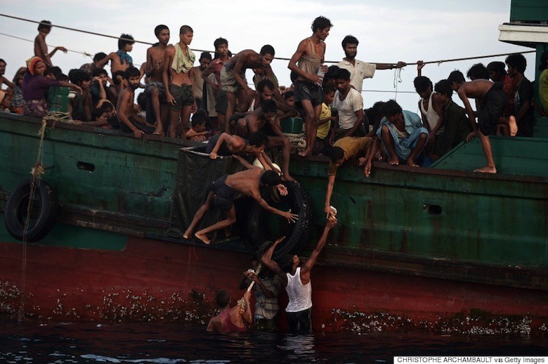 Rohingya migrants pass food supplies dropped by a Thai army helicopter to others aboard a boat drifting in Thai waters off the southern island of Koh Lipe in the Andaman sea on May 14, 2015. A boat crammed with scores of Rohingya migrants -- including many young children -- was found drifting in Thai waters on May 14, with passengers saying several people had died over the last few days. AFP PHOTO / Christophe ARCHAMBAULT (Photo credit should read CHRISTOPHE ARCHAMBAULT/AFP/Getty Images)