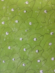 Illustrated page of a book filled with green lizards looking at the top right hand corner