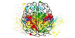 illustration of a brain with lots of bright colours, red, green, blue and yellow, splashed on it
