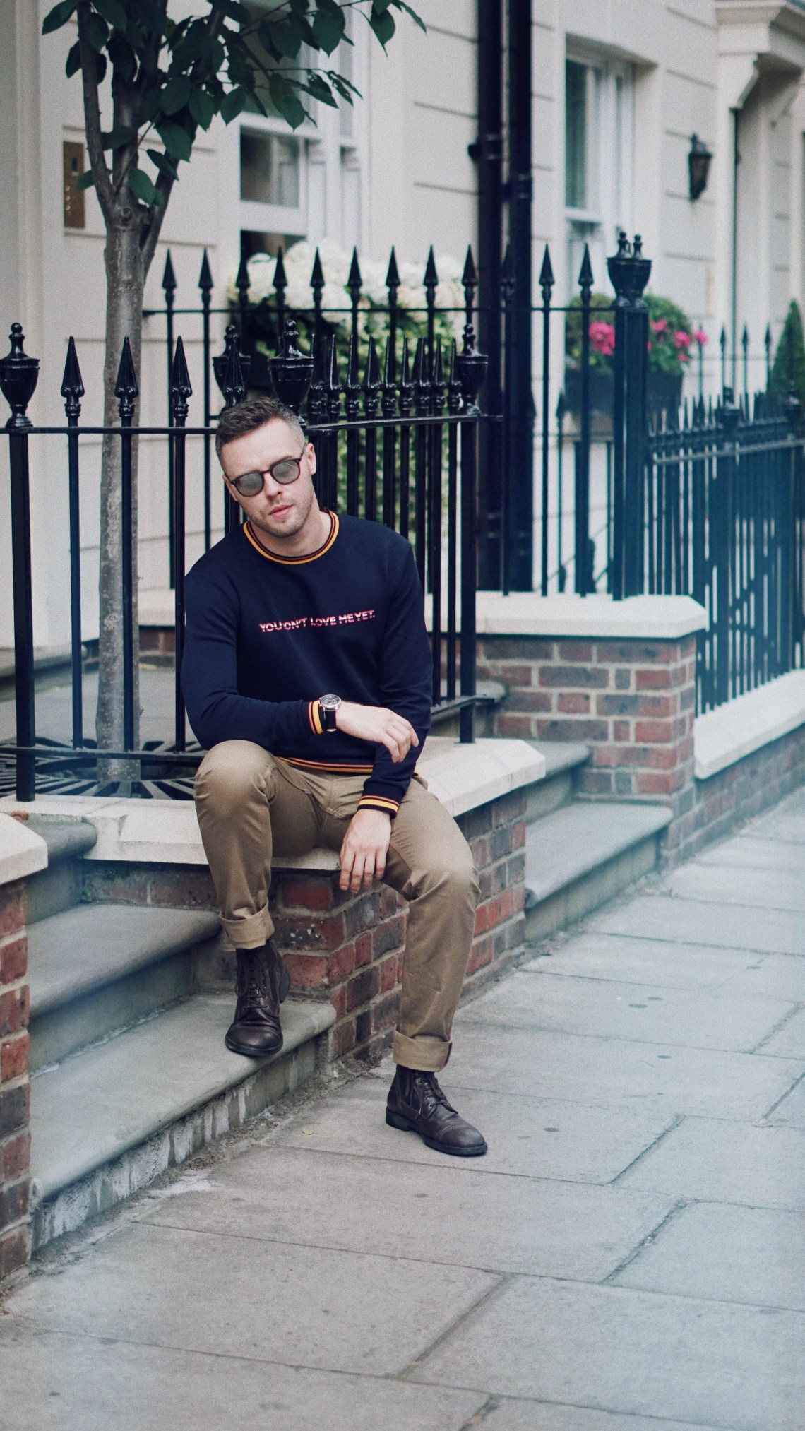 Shady Whittaker. Wearing EYKI Watch from TrendHim, Zara Sweatshirt, Zara Trousers in Khaki, Sunglasses from Garrett Leight California Optical and Geox Boots. Blog by Skirmantas Petraitis.