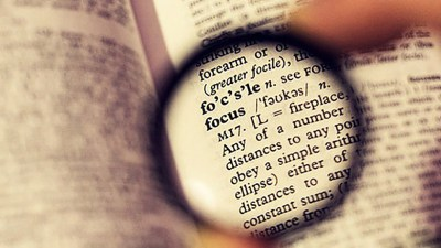 lens enlarging the word 'focus' in a dictionary