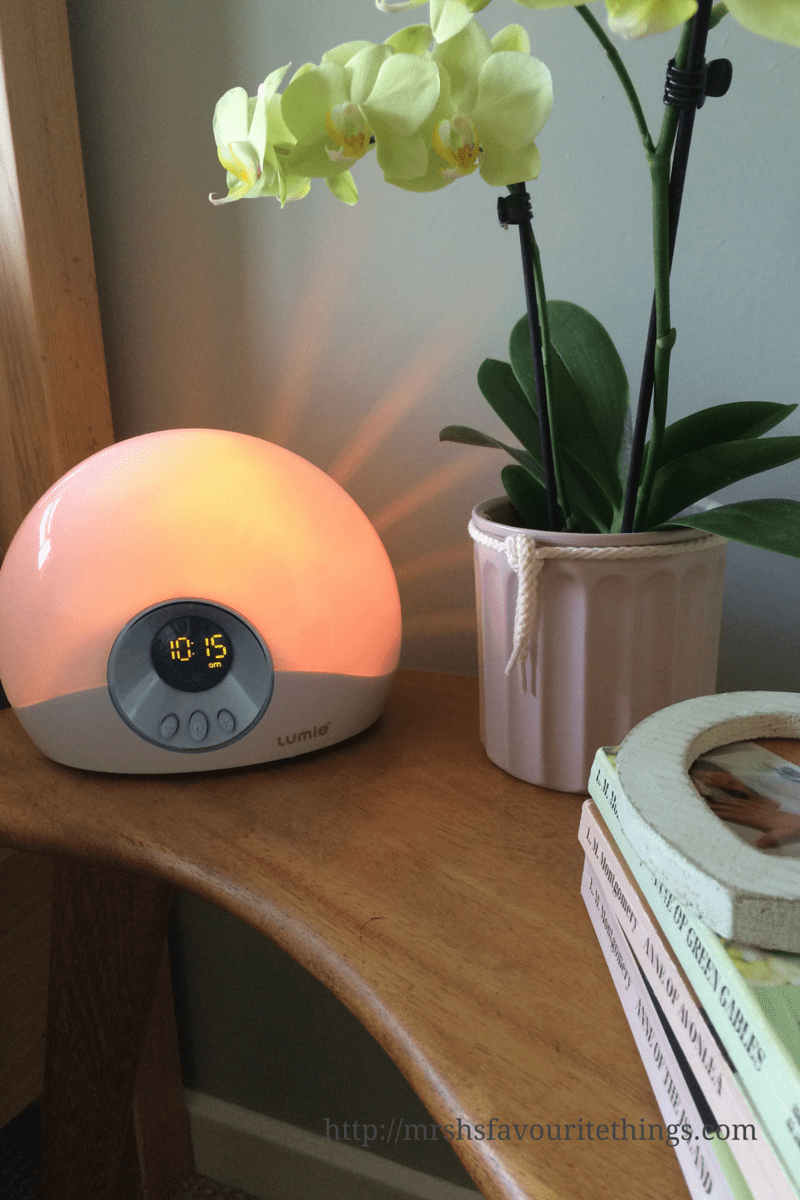 A Lumie Bodyclock STARTER 30 on a bedside table with an orchid and 3 books and a heart shaped picture frame_Wake up brighter: Lumie Bodyclock STARTER 30 review_Mrs H's favourite things