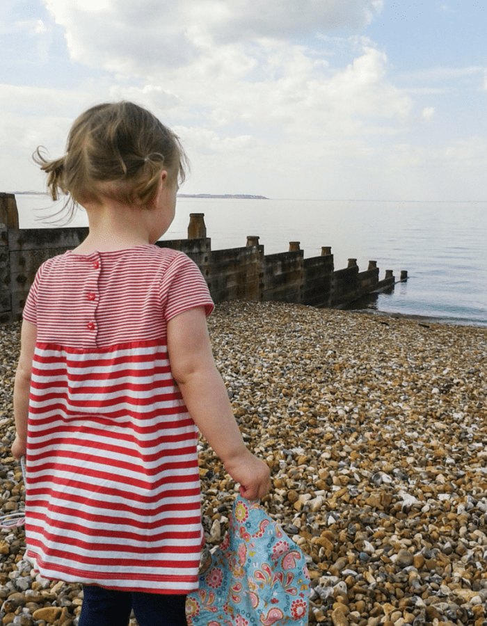 A little girl, wearing a red and white striped dress and with bunches in her hair stands on a pebbly beach and looks out across the break water at the sea _ My Captured Moment - My five favourite photographs from 2015- Mrs H's favourite things -