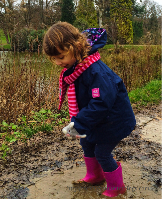 A little girl in warm weather gear jumps in muddy puddles in front of a lake in a park _ Days out in the winter sunshine - My Captured Moment_Mrs H's favourite things