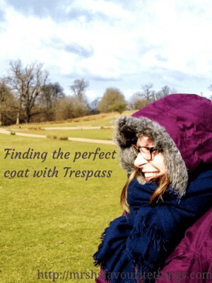 "A woman stands in front of the grounds of a stately home, she has a warm winter coat by Trespass on, with the hood up and accessorised with a navy scarf _ includes the title ""Finding the perfect coat with Trespass"" _ Mrs H's favourite things"