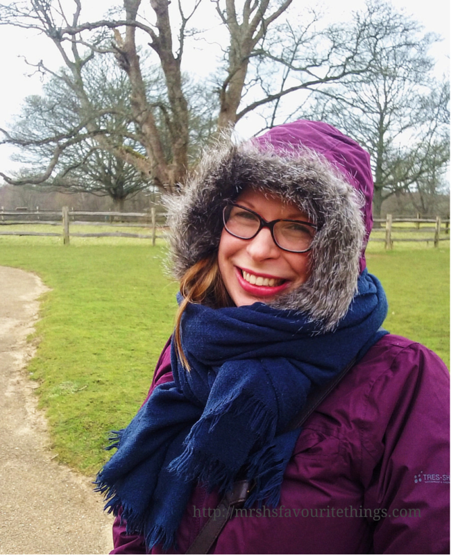 A woman stands in front of the grounds of a stately home, she has a warm winter coat by Trespass on, with the hood up and accessorised with a navy scarf _ Finding the perfect coat with Trespass _ Mrs H's favourite things