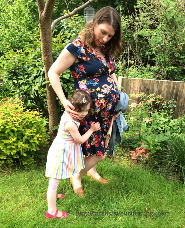 A photograph of a pregnant lady standing in a garden wearing a floral maternity dress from Tiffany Rose, whilst being hugged by her 3 year old daughter _ What I wore ... for afternoon tea at the Savoy ... when 32 weeks pregnant _ Mrs H's favourite things