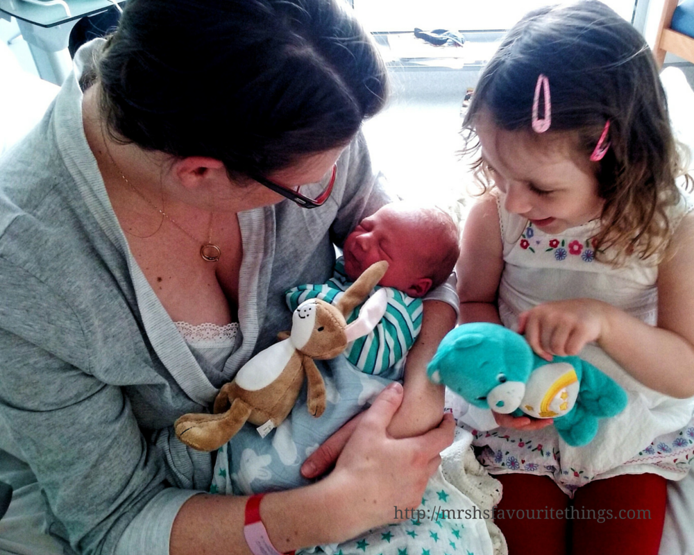 A mum sits on a hospital bed with her three year old daughter as she looks adoringly at her newborn baby brother for the first time - Mrs H's favourite things - A heart full of love - The Siblings a Project - July 2016