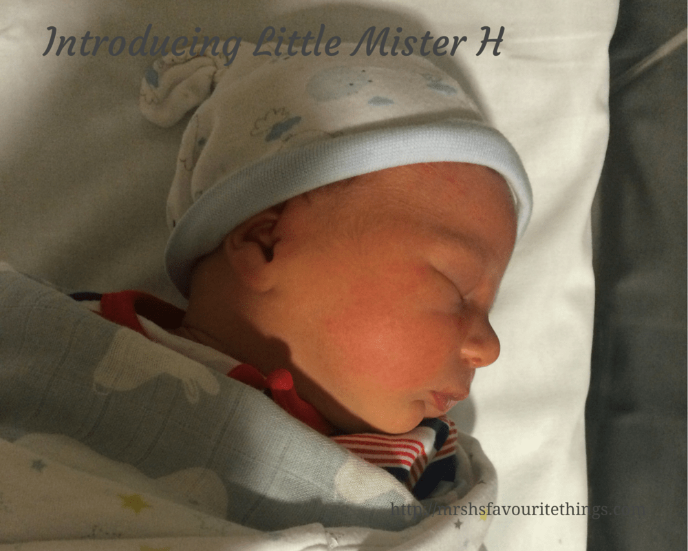 "A beautiful newborn baby boy is sleeping peacefully in a cot. He is wearing a little hat, stripey sleepsuit and has both a lightweight star blanket and bunny rabbit swaddling blanket _ includes the title ""Introducing Little Mister H""_Mrs H's favourite things"
