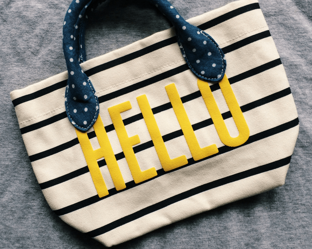 "A photo of a small GAP Kids tote bag - a navy and white stripped canvas bag with a denim and white polka dot handle and the word ""hello"" appliqued on in bright yellow - Mrs H's 10 favourite things - May/ June/ July 2016 - Mrs H's favourite things"