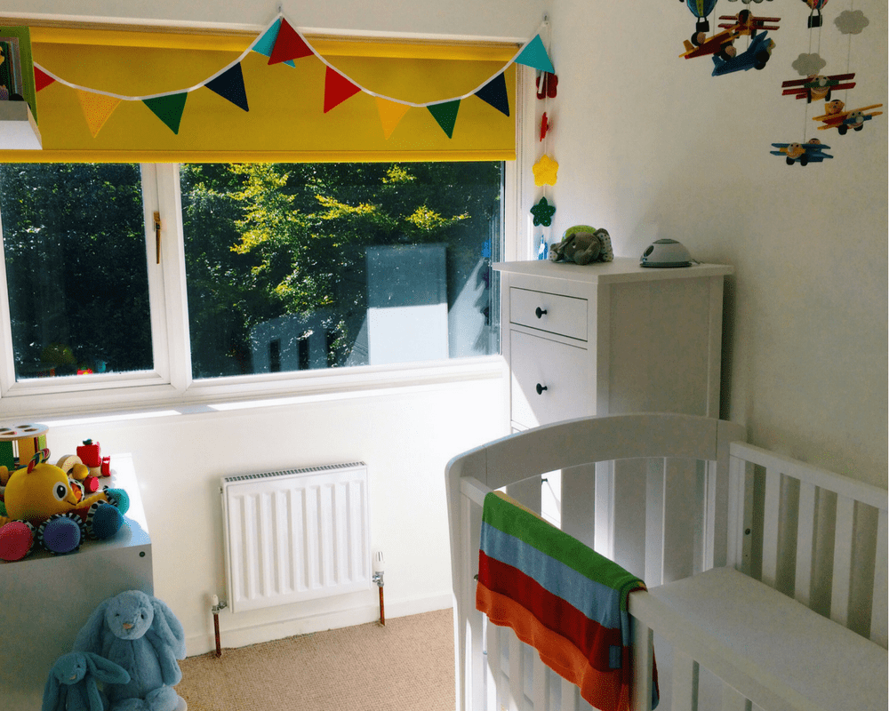 A photograph of a rainbow themed nursery. The room includes white walls and furniture and many rainbow coloured accessories _ Little Mister H's rainbow themed nursery - a tour and vlog - Mrs H's favourite things