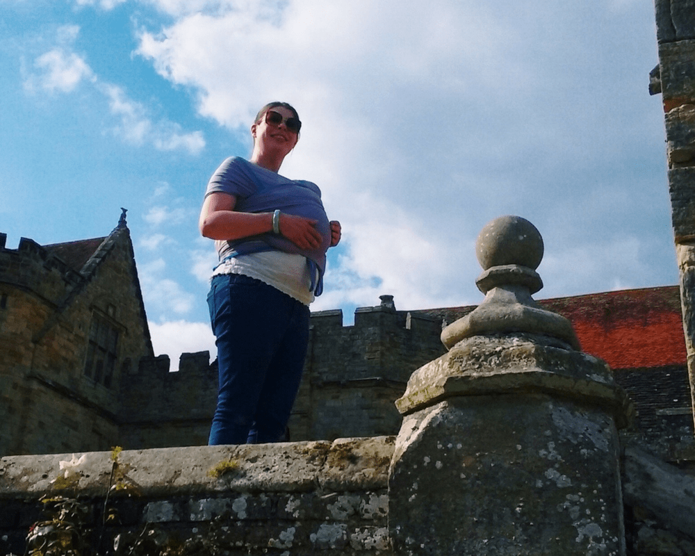 A photograph of a lady with brown hair and wearing sunglasses standing in front of the palace at Penshurst Place and wearing her snoozing baby in the Wuti Wrap from the brand We Made Me - We made Little Mister H - Mrs H's favourite things