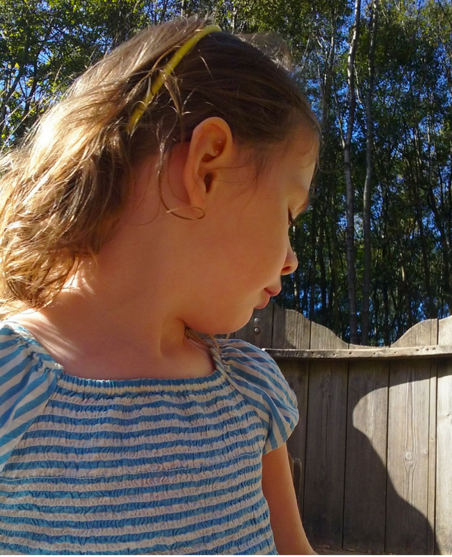A photograph of a profile of a beautiful little girl. In the background are blue skies and lush green trees_My rainbow baby_Mrs H's favourite things