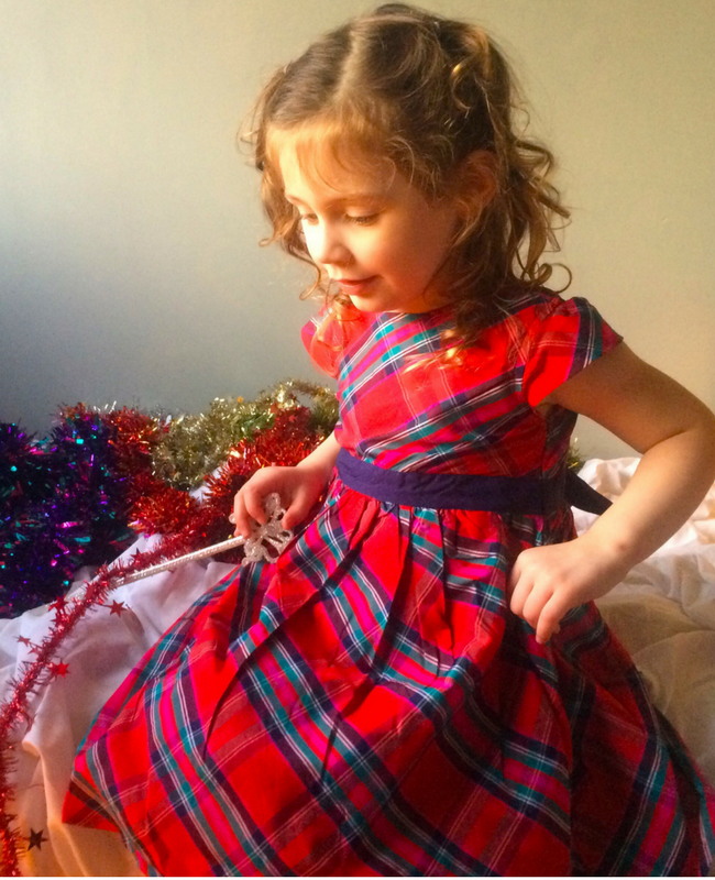 A photograph of a pretty little girl wearing a red tartan party dress from JoJo Maman Bébé and sitting on a bed playing with a fairy wand and some tinsel - Christmas outfits from JoJo Maman Bébé- Mrs H's favourite things