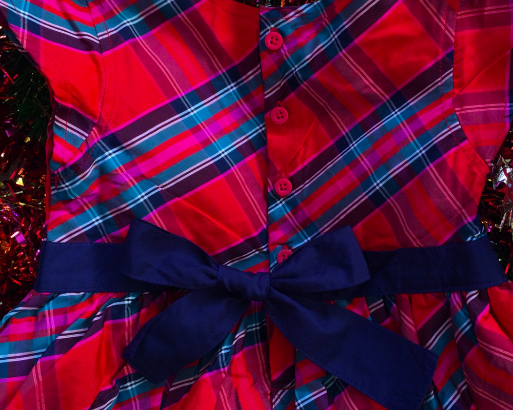 A photograph of the back of a red tartan party dress from JoJo Maman Bébé showing the buttons down the back and the contrasting sash ties in a bow - Christmas outfits from JoJo Maman Bébé - Mrs H's favourite things