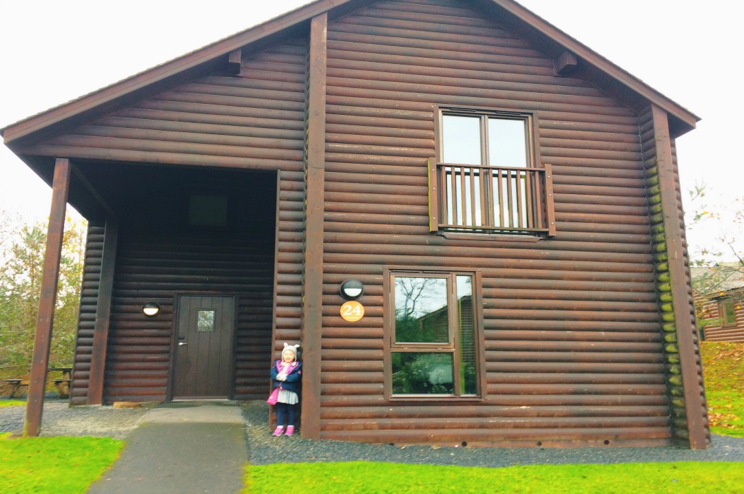 A photograph of a little girl standing in front of a Skomer Lodge at Bluestone National Park Resort, Pembrokeshire, Wales _ Mrs H's favourite things