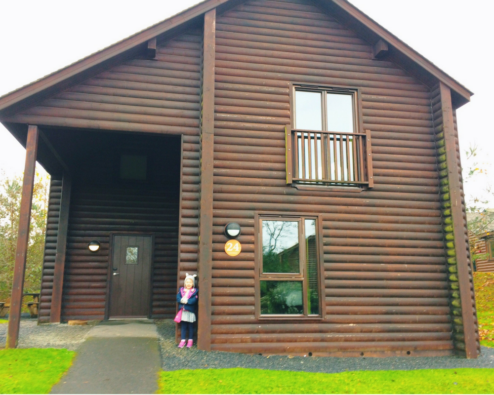 A photograph of a little girl standing in front of a Skomer Lodge at Bluestone National Park Resort, Pembrokeshire, Wales _ Includes the title of the blog post _ Bluestone Wales - A review of the Resort and Kingdom of the Elves - Mrs H's favourite things