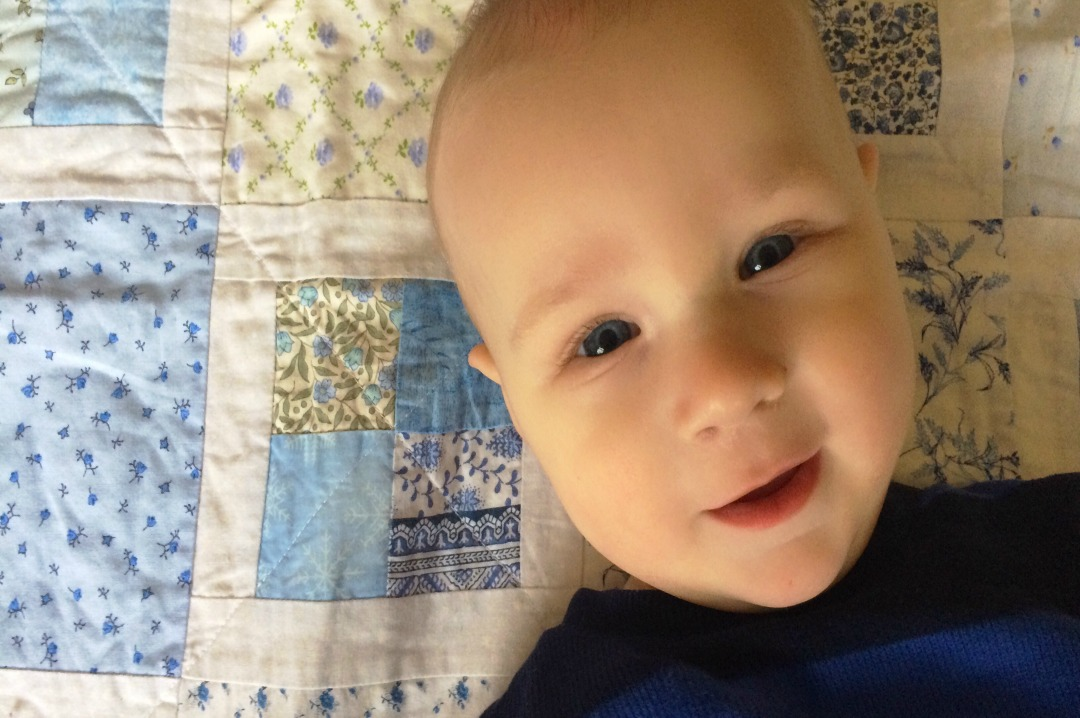 A photograph of a gorgeous 6 month old baby boy lying on a pale blue patchwork blanket and wearing a blue and black stripey top My top 5 teething products _ Mrs H's favourite things