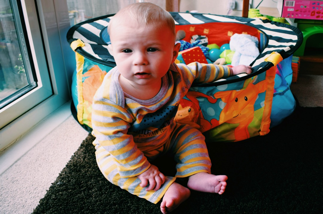 A photograph of our eight month old baby boy wearing a grey and yellow striped personalised dinosaur babygrow from Sgt. Smith, sitting independently and holding on to a brightly coloured ball pit filled with brightly coloured toys - Little Mister H at eight months old - an update - Mrs H's favourite things
