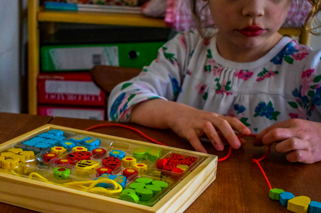 A photograph of a little girl sitting in a living room in her sleep dress playing with a set of the Bigjigs Garden Bead Box and threading the beads carefully onto a cord - Bigjigs Play Patrol Rainbow Rattle and Garden Bead Box - Mrs H's favourite things