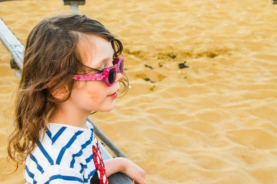 A photograph of a little girl standing on a beach in Broadstairs Kent, she has sand on her face and the wind is blowing her hair and she is happy - Our week in Broadstairs, Kent - Mrs H's favourite things