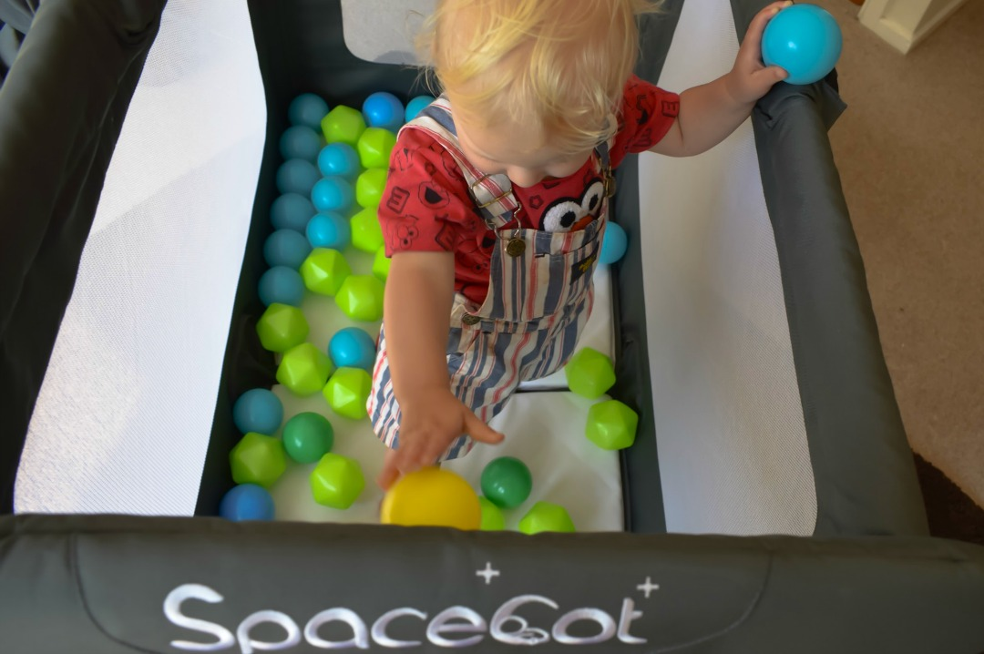 A photograph of a 14 month old playing in his SpaceCot travel cot a fantastic product needed to make Travelling With Children a less stressful business - 7 Essential Products To Make Travelling With Children Stress-free - Mrs H's favourite things