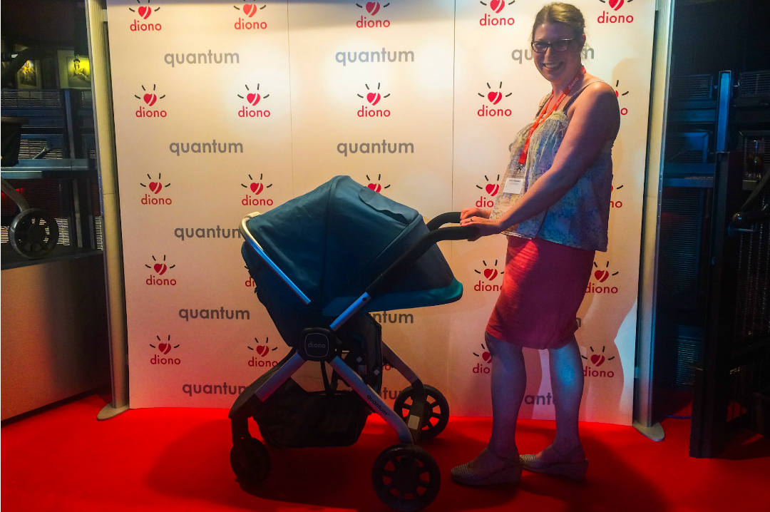 A photograph of a lady standing and posing with a teal Diono Quantum travel system on the red carpet and the launch of the Diono Quantum - #AdventureReady with the Diono Quantum travel system - the launch and first impressions - Mrs H's favourite things