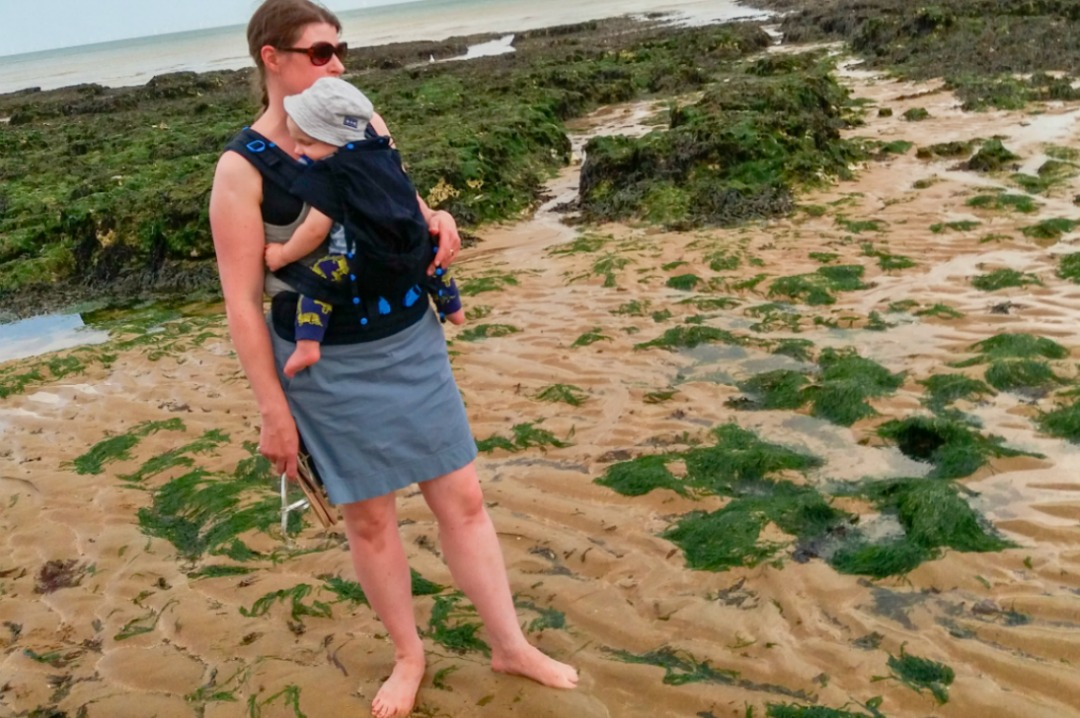 A photograph of a mother and baby standing on Louisa Beach in Broadstairs Kent - the baby is being carried by his mum in a Pao Papoose 3 in 1 front and back baby carrier in midnight black from We Made Me - Pao Papoose by We Made Me - A Review of the 3 in 1 Front and Back Baby Carrier - Mrs H's favourite things