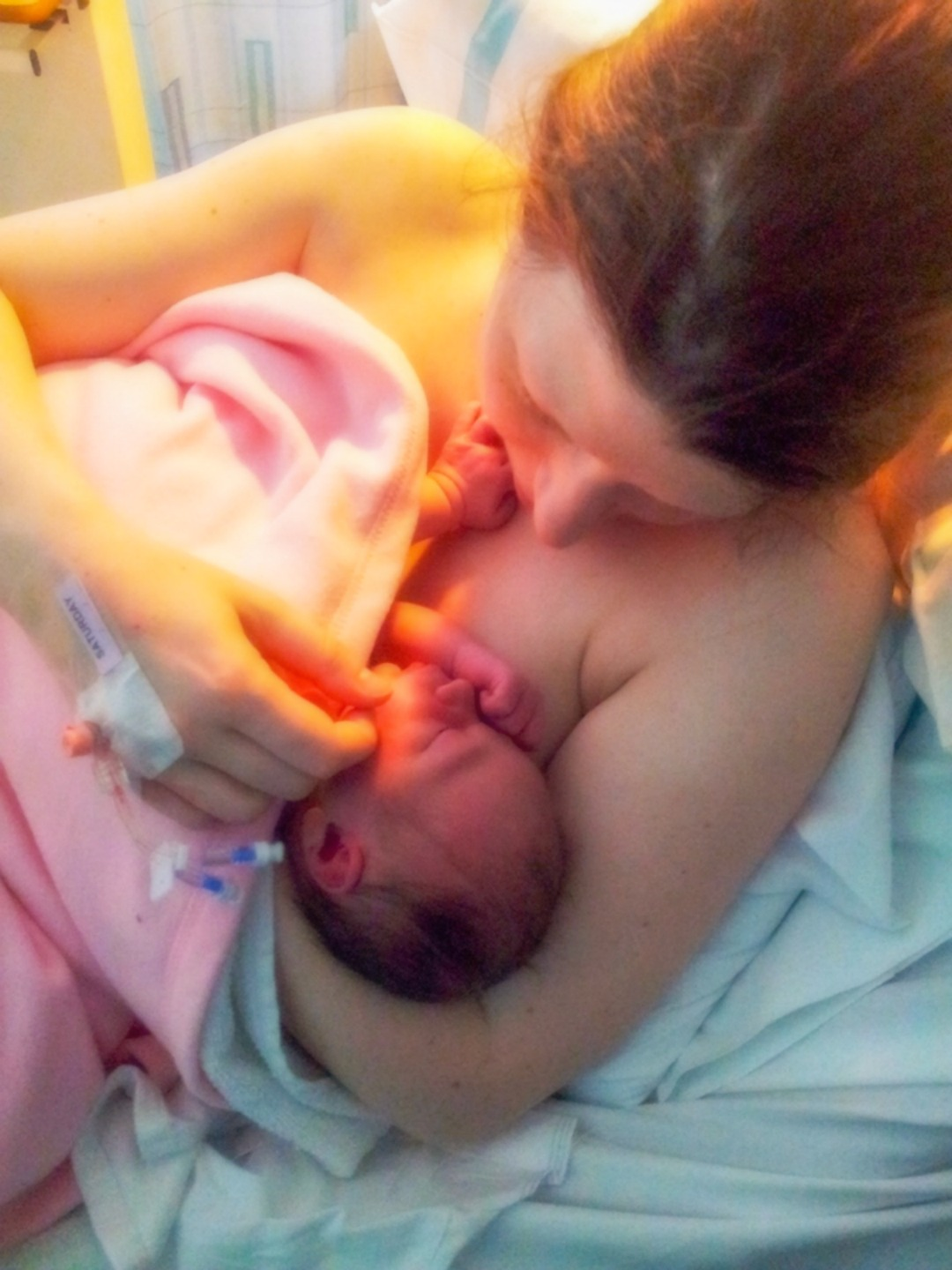 A photograph of a mum giving skin to skin to her newborn daughter who is wrapped in a pink blanket - The Sadness of Not Being Able to Breastfeed my Babies - Mrs H's favourite things