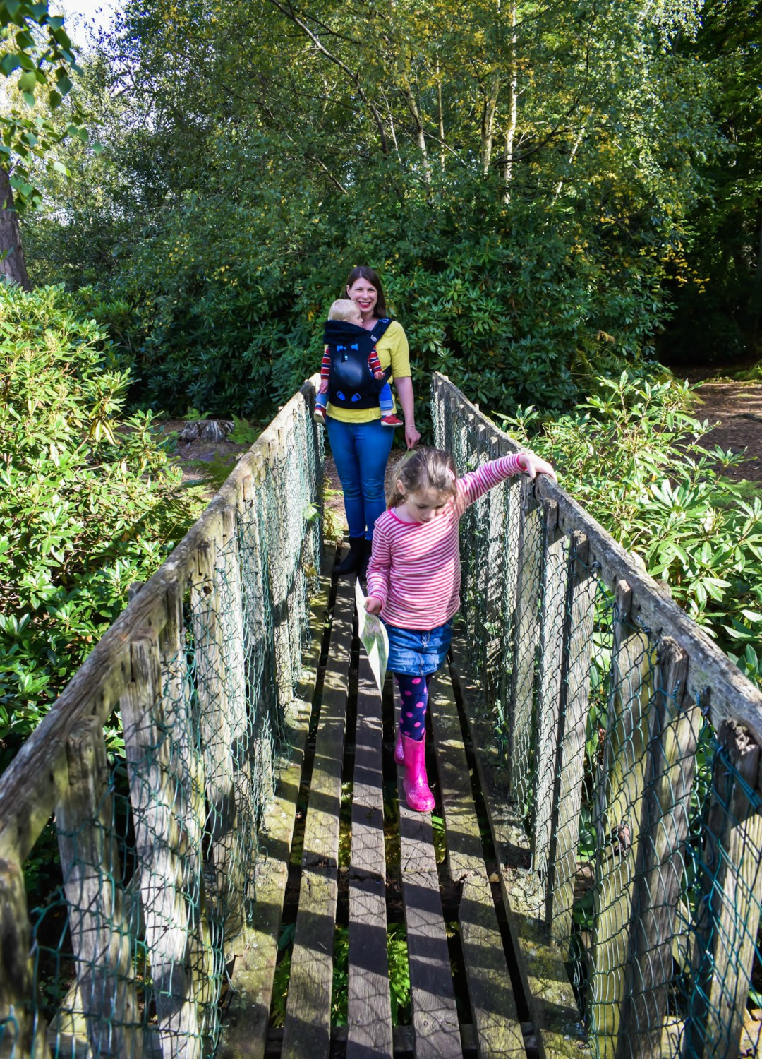 A photograph of a mother carrying her 14 month old son in the Pao Papoose Baby Carrier and walking across a rickety wooden bridge at the High Rocks in Tunbridge Wells - she is being led by her 4 and a half year old daughter - 39 Life Lessons for 39 Years - Mrs H's favourite things
