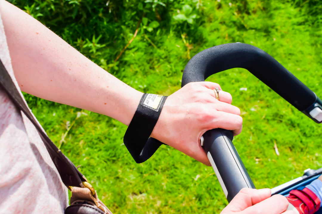 A photograph of the hands and arms of a woman pushing the Diono Quantum Travel System - the photo demonstrates the 6-position handle bar and safety strap for the buggy - Diono Quantum Travel System - A Review - Mrs H's favourite things