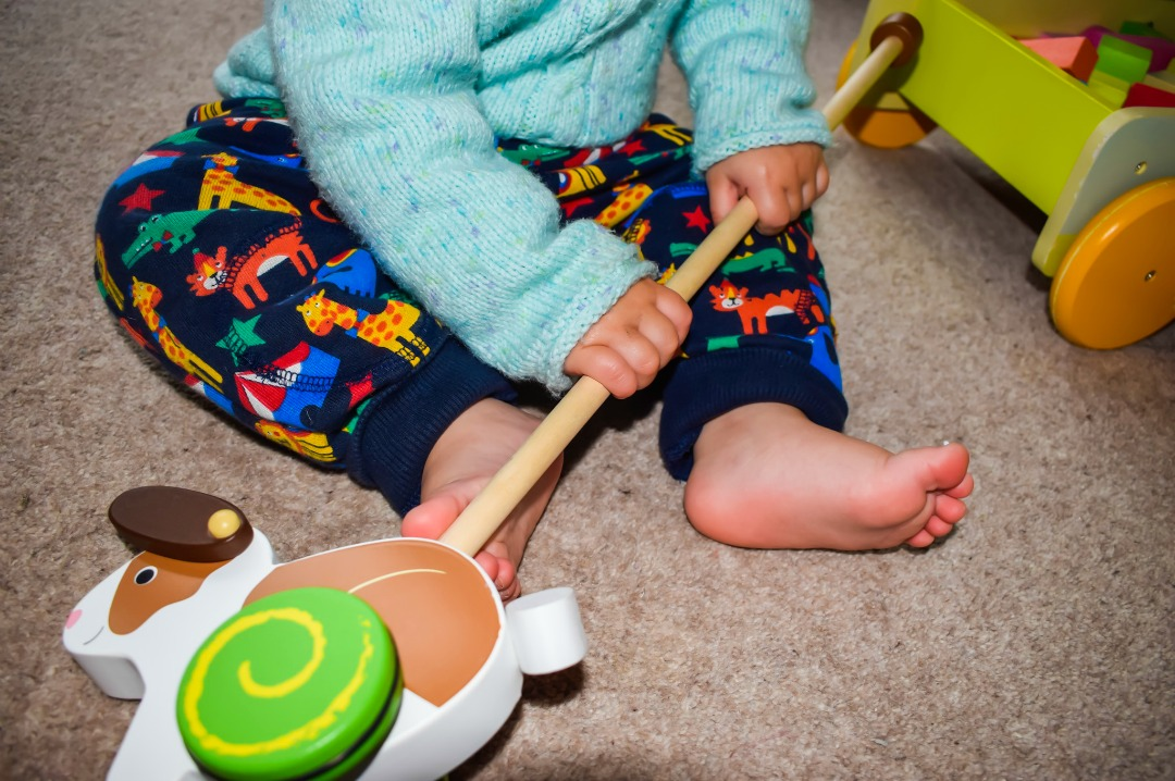 A 14 month old boy sitting on the floor (the photograph only shows his legs and torso) and holding onto a wooden push-along rabbit toy from Bigjigs - Bigjigs Sweetland Express and Push-Along Rabbit - A Bigjigs Play Patrol Review - Mrs H's favourite things