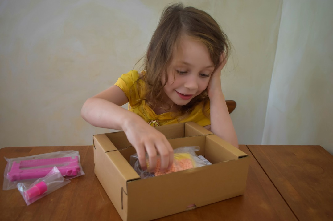 A photograph of a little girl (she is four years old), dressed as the Disney Princess Belle, opening up the box containing her Aquabeads Disney Princess Playset - Aquabeads Disney Princess Playset - a review of this brilliant quiet time activity for busy children - Mrs H's favourite things