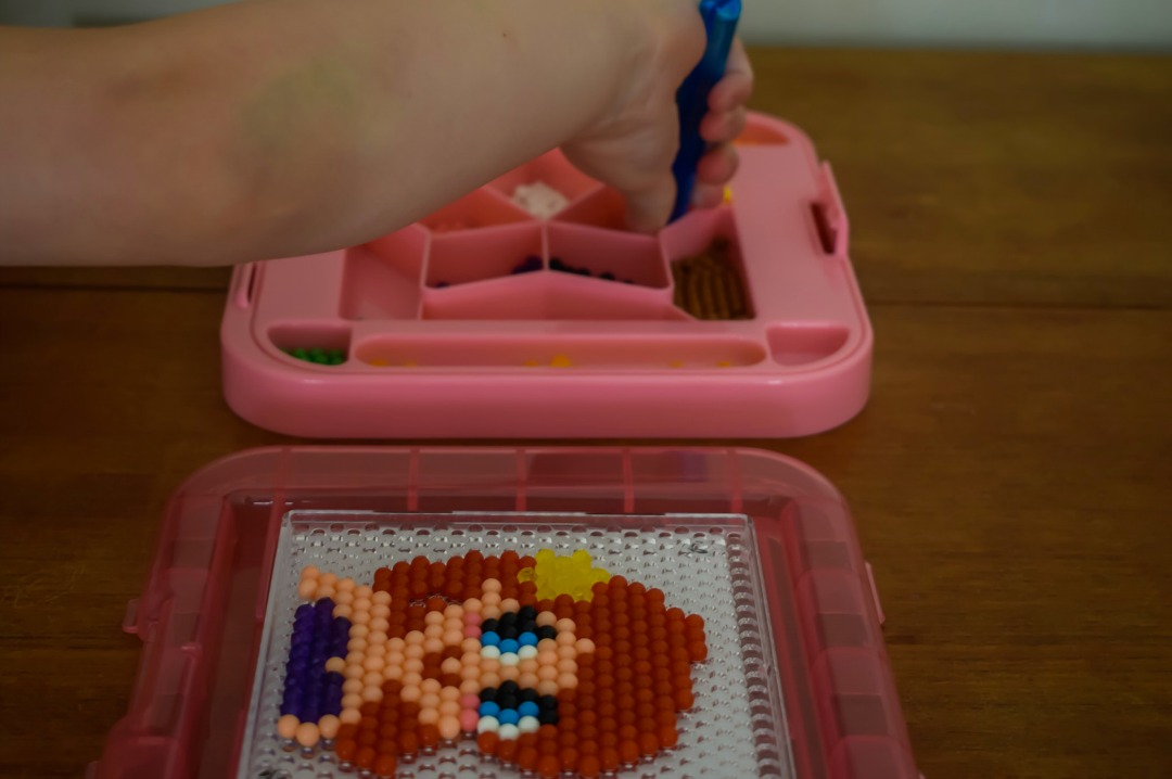 A photograph of the hand of a little girl (she is four years old) using a set of Aquabeads tweezers to pick up some beads to make the Disney Princess Ariel form her Aquabeads Disney Princess playset - Aquabeads Disney Princess Playset - a review of this brilliant quiet time activity for busy kids - Mrs H's favourite things