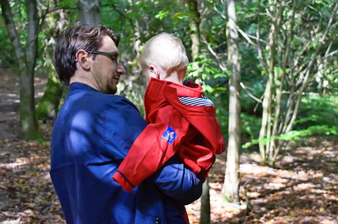 A photograph of a 15 month old baby boy and his Daddy are going for a walk in the woods - the little boy is being carried in his Daddy's arms and they have their backs to the camera - the little boy is wearing clothes from JoJo Maman Bebe including the red children's Fisherman's Jacket - Little Mister H's First Walk in the Woods with JoJo Maman Bebe - Mrs H's favourite things