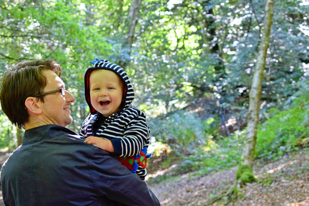 A photograph of a 15 month old boy and his Daddy on a walk in the woods - the little boy is in his Daddy's arms and is being kissed gently on the cheek - the little boy is wearing clothes from JoJo Maman Bébé including the Stegasaurus Zip-Up Hoodie - Little Mister H's First Walk in the Woods with JoJo Maman Bébé - Mrs H's favourite things