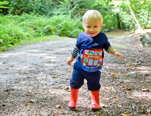 A colourful photograph of a little boy of 15 months old walking in the woods and wearing JoJo Maman Bébé clothes - including red wellie boots, a dino bus tour applique t-shirt and cosy baby joggers - the sun is shining and the little boy has a smile on his face - Little Mister H's first walk in the woods with JoJo Maman Bébé - Mrs H's favourite things