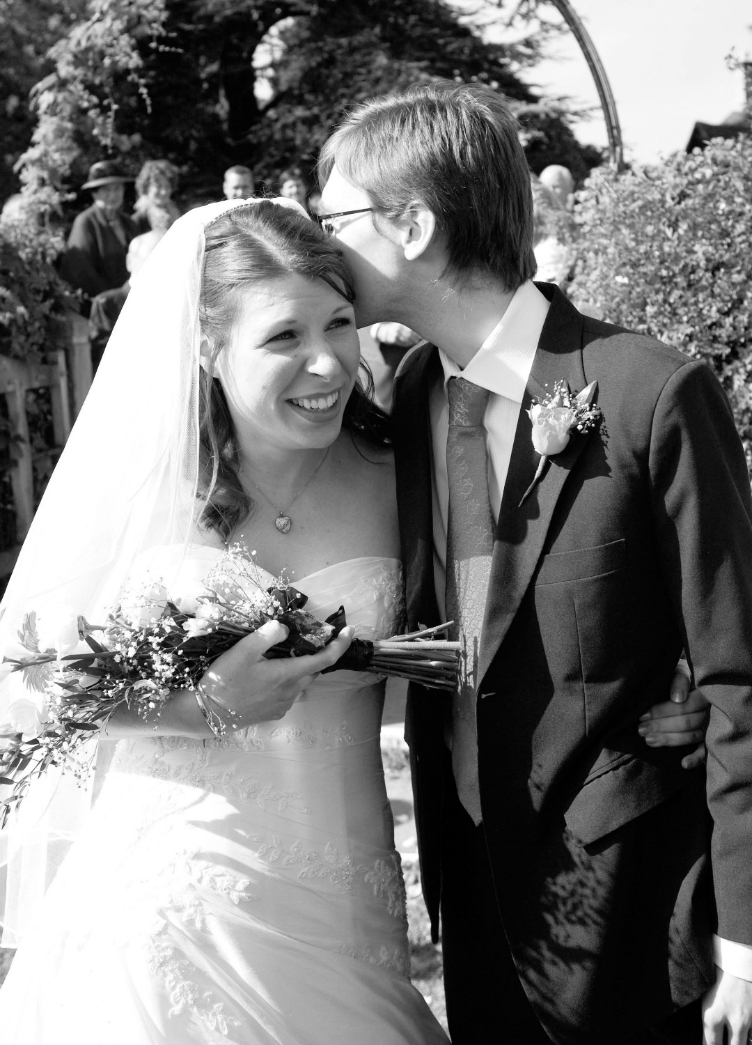 A photograph of a bride ad groom on their wedding day - the groom is kissing the bride on her head and she is smiling - Nine Reasons Why I Love You - Mrs H's favourite things