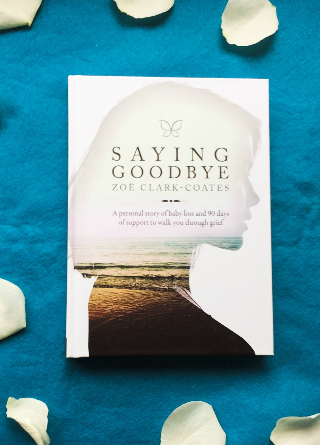A flat lay photograph of the book Saying Goodbye by Zoë Clark-Coates - A Personal Story about baby loss - the book is lying on some blue felt and is surrounded by white rose petals - Saying Goodbye by Zoë Clark-Coates - A review and an interview with the author - Mrs H's favourite things