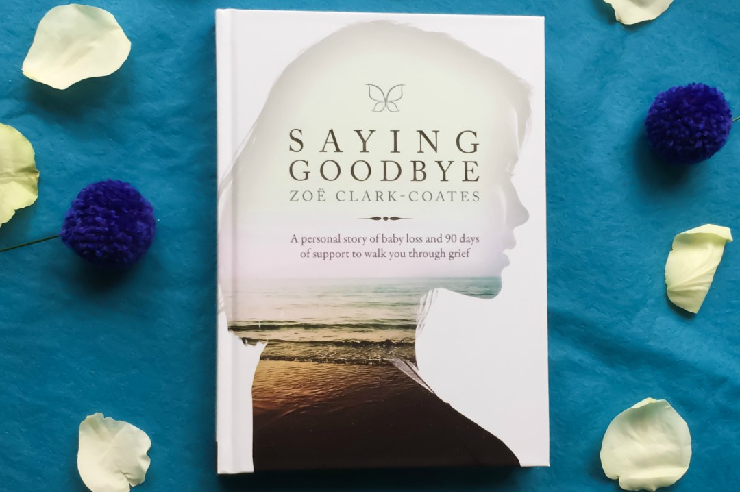 A flat lay photograph of the book Saying Goodbye by Zoë Clark-Coates on a piece of blue felt surrounded by white rose petals and blue pom pom flowers - Saying Goodbye by Zoë Clark-Coates - A Review and Interview with the Author - Mrs H's favourite things