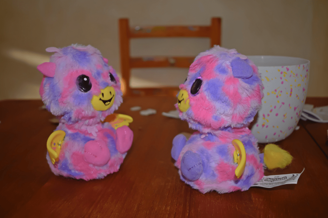 A photograph of pink and purple Giraven twins from Hatchimals Surprise sitting on a dining room table and interacting together - Reviewing the brand new Hacthimals: Hatchimals Surprise - Mrs H's favourite things