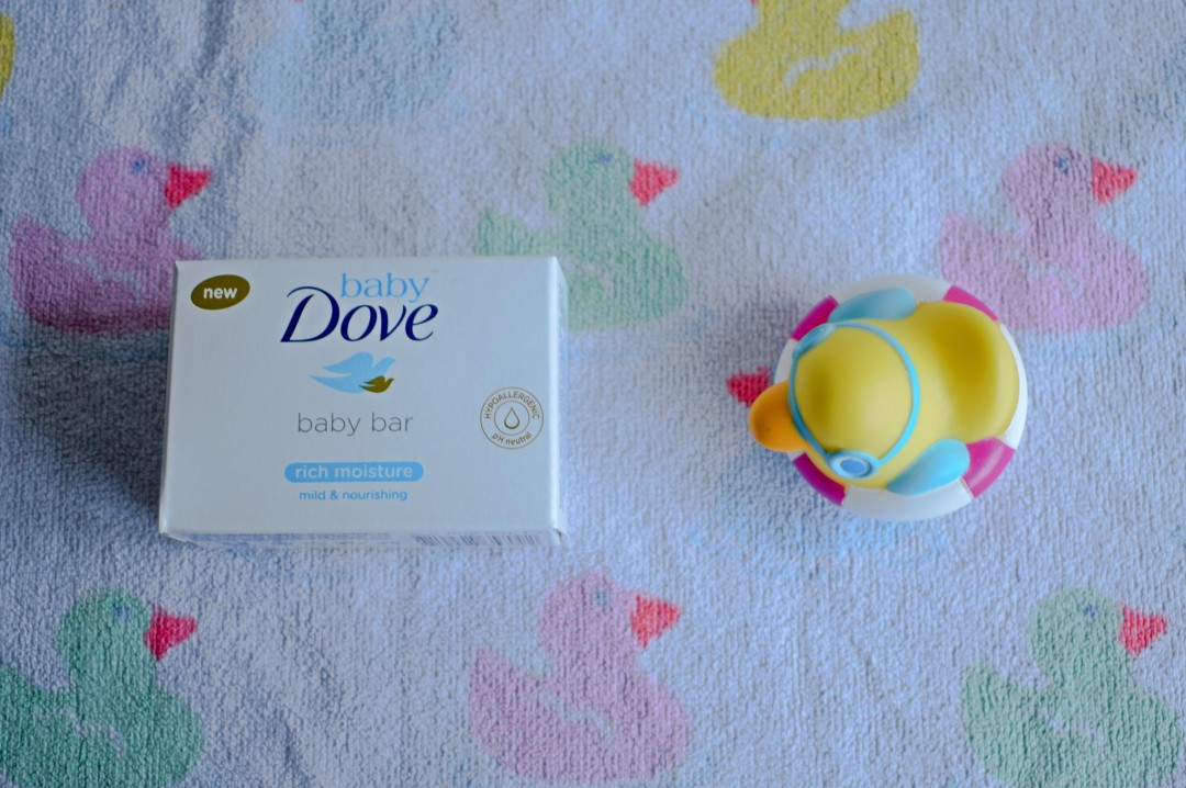 A photograph of a Real Moisture Bar from Baby Dove lying on a towel covered in a pattern of pink, green, blue and yellow ducks and a rubber duck - Caring For My Baby My Way With Baby Dove - Mrs H's favourite things