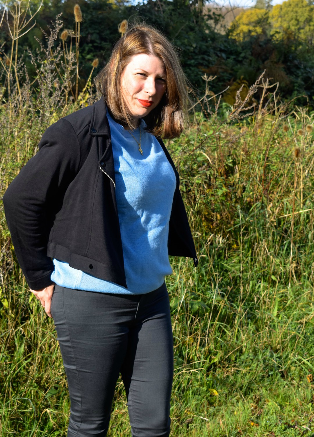 A photograph of a young brunette woman standing outside and wearing a blue ruffle sleeve jumper from JD Williams, a black Jersey Biker Jacket from JD Williams and grey skinny jeans and a pair of grey ankle boots - this is a photo of her modelling her new Mummy Style - Finding My Mummy Style With JD Williams and their Autumn/ Winter Collection - Mrs H's favourite things