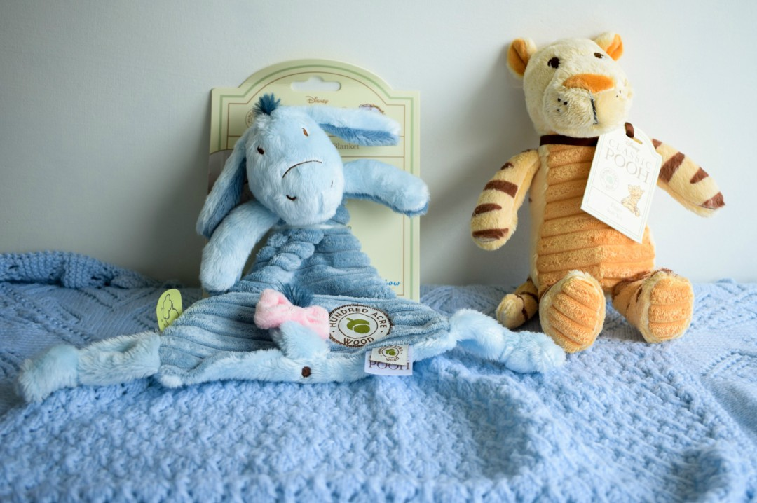 A photograph of the Eeyore Comfort Blanket and Tigger Soft Toy from the Classic Winnie the Pooh Toy collection from Rainbow Designs. These toys are leaning against a wall and sitting on a soft blue baby blanket -