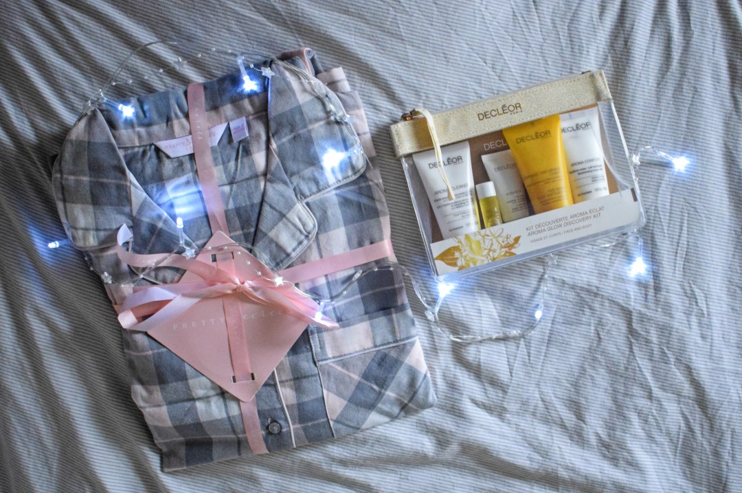 A photograph of a new pair of checked grey and light pink pyjamas and a pack of Decleor beauty goodies - 5 Steps to the Perfect Pamper - Mrs H's favourite things