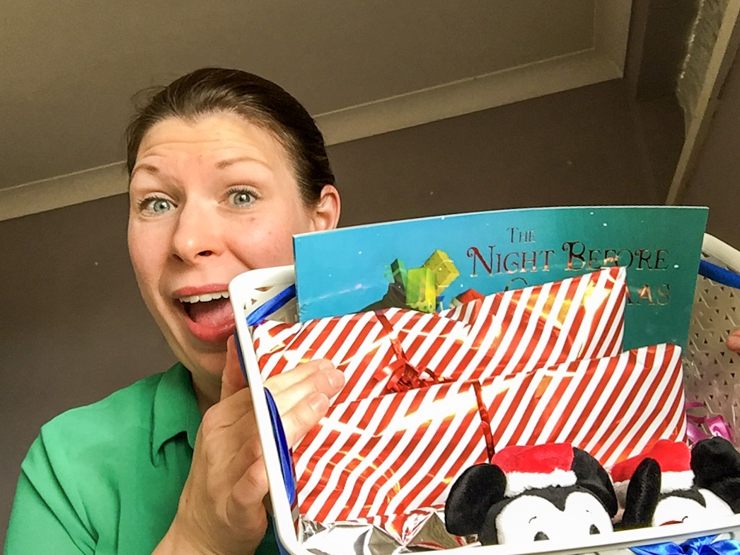 A photograph of a young woman pulling a funny face and holding up a basket which is her packed Christmas Eve box - it is filled with wrapped presents, soft toys, books and chocolate - Our Christmas Eve box - what's inside? - Mrs H's favourite things
