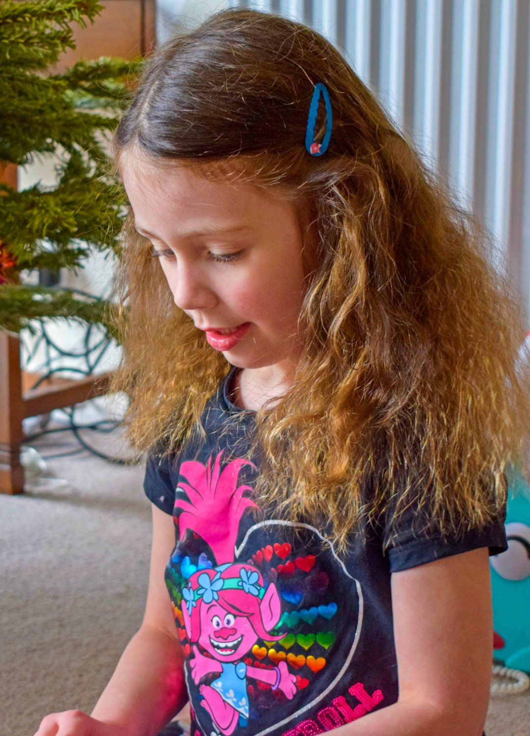 """A photograph of a little girl sitting in front of a Christmas tree and wearing a Trolls t-shirt from George at ASDA. The t-shirt features a motif of Princess Poppy from Trolls and the slogan """"Out of con-TROLL"""" - Having a Troll-tastic Christmas with Trolls Holiday -Mrs H's favourite things"""
