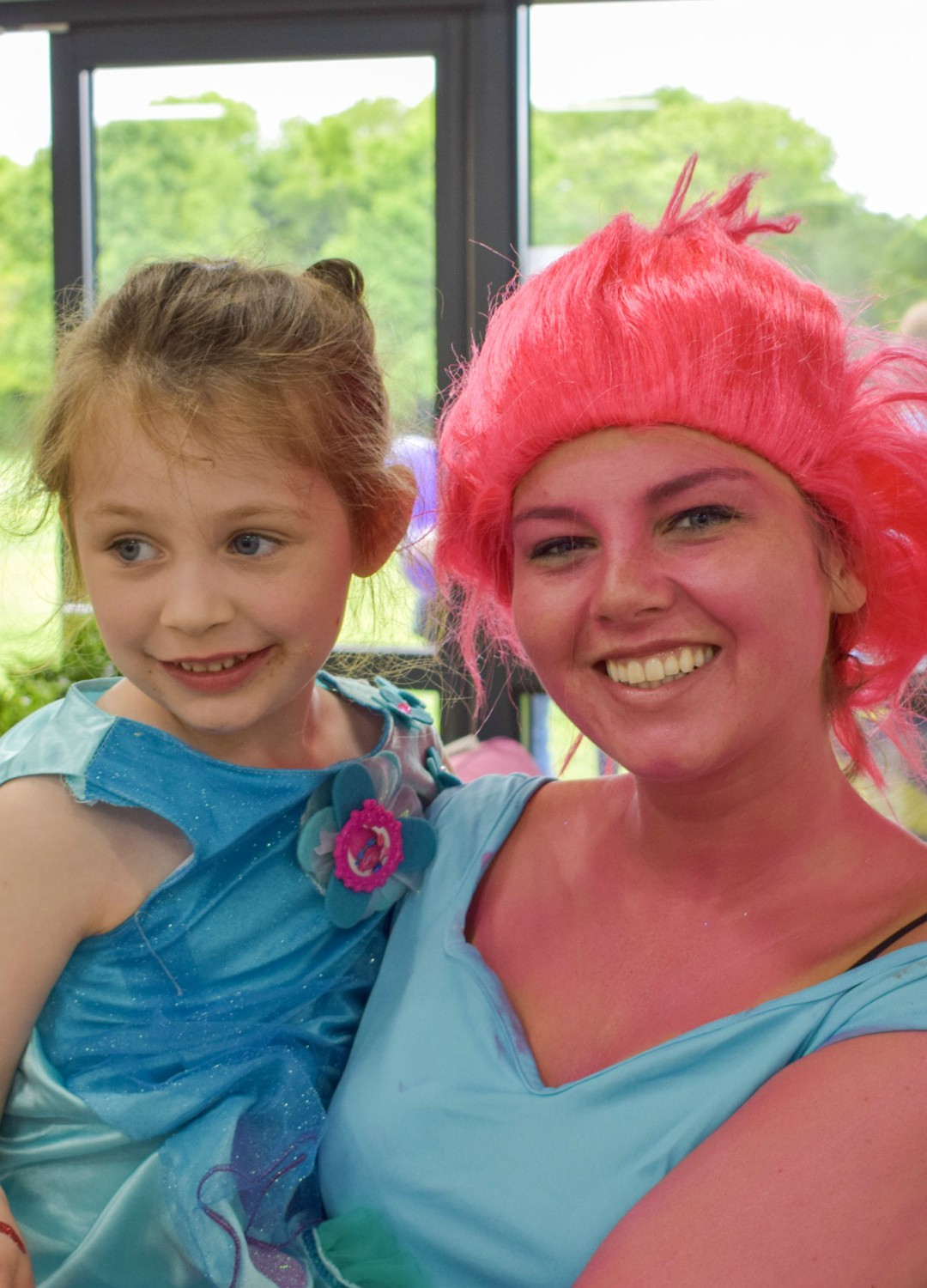 A photograph of a little girl dressed up as Princess Poppy from Trolls at her birthday party, she is being given a hug by a party entertainer who is also dressed up as Princess Poppy from Trolls (including pink bodypaint and a pink wig) - Having a Troll-Tastic Christmas with Trolls Holiday - Mrs H's favourite things