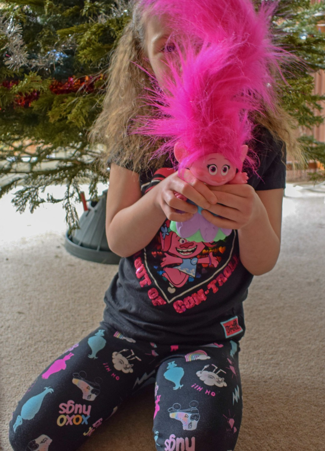 A photograph of a little girl sitting in front of a Christmas tree. She is wearing a Trolls t-shirt from George in ASDA. She is also holding a copy of Trolls Holiday - Having a Troll-tastic Christmas with Trolls Holiday - Mrs H's favourite things